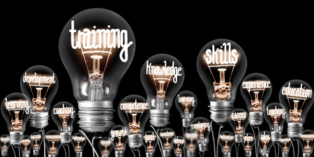 Foto von Glühbirnen mit leuchtenden Fasern in Form von TRAINING, FÄHIGKEITEN und WISSEN Konzeptbezogene Wörter einzeln auf schwarzem Hintergrund Standard-Bild