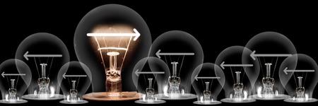 Gran grupo de bombillas brillantes y atenuadas con fibras en forma de flechas aisladas sobre fondo negro; concepto de innovación y cambio