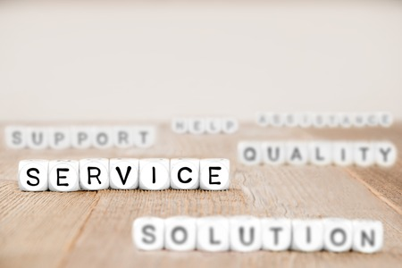 White cube blocks with Service, Solution, Quality and Support words imprinted on cube surface, focused on Service cubes