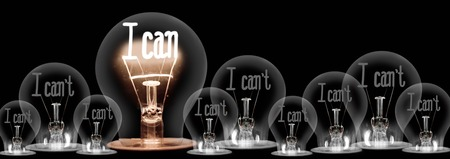 Large group of shining and dimmed light bulbs with fibers in a shape of I Can't and I Can words isolated on black background; concept of Motivation, Positivity and Change