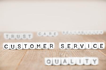 Bloques de cubo blanco con palabras relacionadas con el concepto de servicio al cliente, calidad, confianza y cuidado en la superficie de madera Foto de archivo