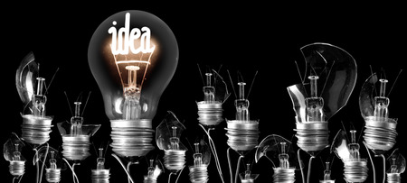 Group of proken light bulbs and shining one of them with fiber in IDEA shape isolated on black background; concept of Idea, Innovation and Success