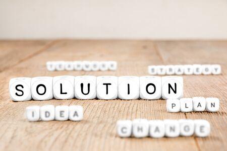 Weiße Würfelblöcke mit Strategie-, Teamwork-, Vertrauens- und Plankonzeptwörtern aufgedruckt. Fokussierte od Strategiewürfel.