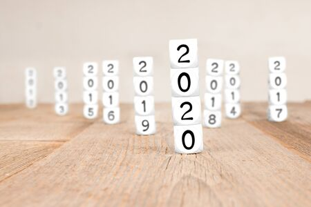 White cube blocks with 2020, 2019, 2018, ..., 2012 imprinted. Focused on 2020. Concept of new year and time.