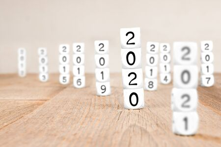 White cube blocks with 2020, 2021, 2019, 2018, ..., 2012 imprinted. Focused on 2020. Concept of new year and time.
