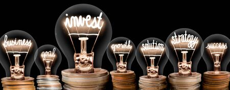 Group of light bulbs on coin stacks with shining fibers in a shape of Invest, Strategy, Business and Solution concept related words isolated on black background Stok Fotoğraf