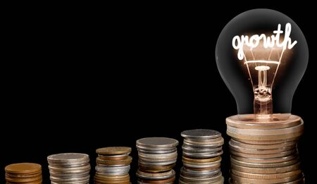 Group of coin rows and light bulb with shining fiber in a shape of Growth concept word isolated on black background