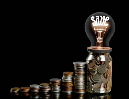 Group of coin rows, glass jar and light bulb with shining fiber in a shape of SAVE concept word isolated on black background