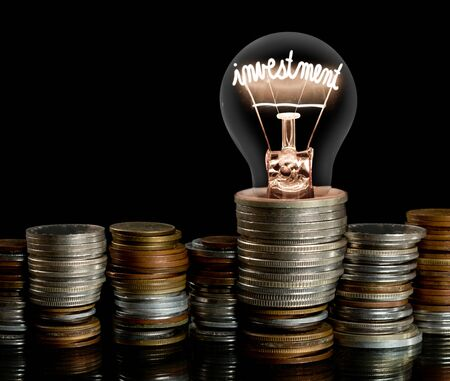 Group of coin rows and light bulb with shining fiber in a shape of Investment concept word isolated on black background