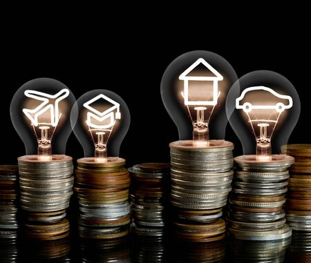 Group of coin rows and light bulbs with shining fibers in a shape of House, Car, Education and Travel icons isolated on black background. Concept of Money Saving, Investment, Mortgage and Insurance.