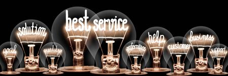 Photo of light bulb group with shining fibers in a shape of Best Service, Business, Solution and Help concept related words isolated on black background Фото со стока