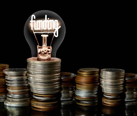 Light bulb on coin stacks with shining fiber in a shape of Funding concept word isolated on black background 스톡 콘텐츠