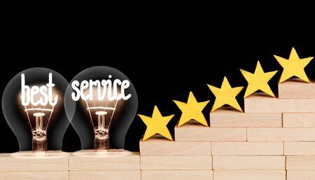Foto von fünf Sternen auf Holzblockleiter und Glühbirnen mit glänzenden Fasern in Form des Best-Service-Konzepts einzeln auf schwarzem Hintergrund.