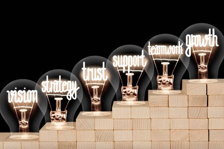 Light bulbs with shining fibers in a shape of Growth, Teamwork and Support concept related words on wooden block ladder isolated on black background.