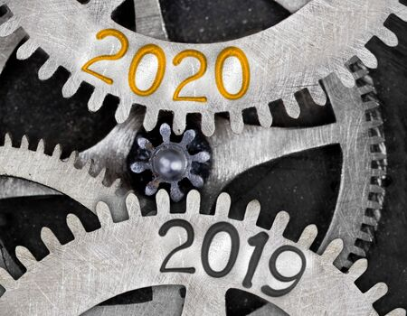 Tooth wheel mechanism with numbers 2020, 2019 imprinted on metal surface. New Year concept.