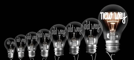 Large group of shining and dimmed light bulbs with fibers in a shape of New and Old Way words isolated on black background. Concept of Innovation, Development and Success Stok Fotoğraf