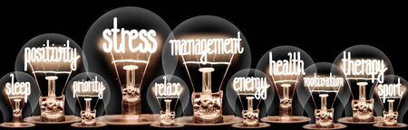 Group of light bulbs with shining fibers in a shape of Stress Management, Health, Therapy and Relax concept related words isolated on black background; horizontal composition