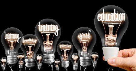 Foto der Glühbirnengruppe mit leuchtenden Fasern in Form von Bildung, Ausbildung, Lernen, Ziel und Wissen Konzeptbezogene Wörter einzeln auf schwarzem Hintergrund