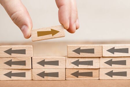 Wooden blocks with gray and brown arrows in opposite directions, one of them hold by a human hand. Concept of Change and Standing Out.