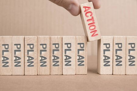 Wooden blocks with black Plan and red Action words imprinted, one of them hold by a human hand. Concept of Decision, Motivation and Success.