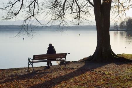 hombre solo: Hombre solitario, sentado junto a un lago