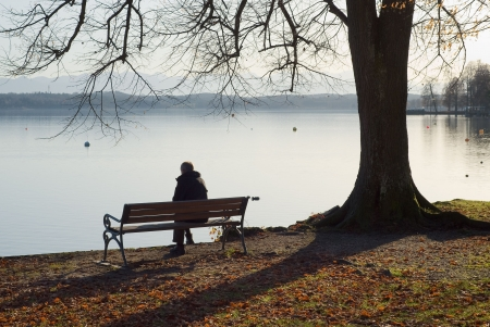 sad lonely: Lonely Man Sitting Next to a Lake