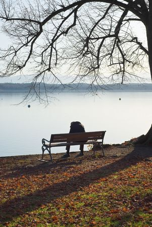 hombre solitario: Hombre solitario, sentado junto a un lago