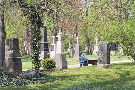 hombre solo: Solitario hombre sentado en un cementerio Foto de archivo
