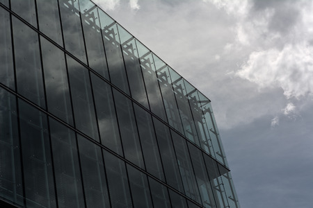 unfavorable: Contemporary Architecture with Sky and Storm Cloud Reflection Stock Photo