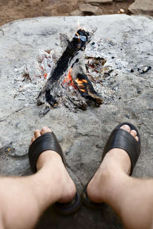 legs open: Adult legs at open campfire