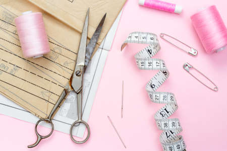 sewing pattern: Shades of pink. Sewing pattern with scissors and tape measure used in fabric