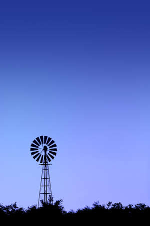 Windmill silhouette during blue hour, dawn. Stock Photo