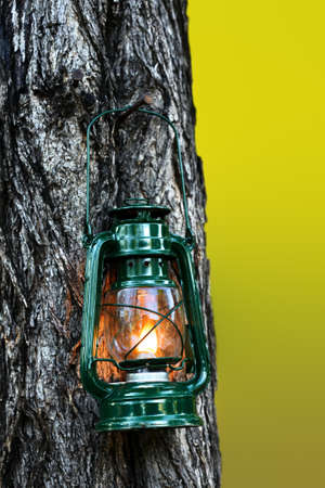 Burning lantern hanging in a Mopani tree in the afternoon. Romantic ambiance created for mood