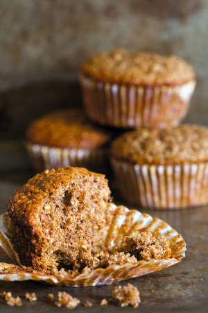 Close up of a bran muffin with crumbs and muffins in the background. Zdjęcie Seryjne