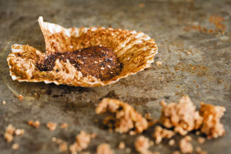 Close-up image of an empty used muffins paper with crumbs lying on surface, demonstrating a finished meal.