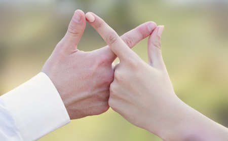 Close-up of caucasian people holding hands in an infinity shape.