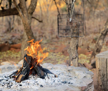 Open wooden campfire in Africa with barbecue grid at the back