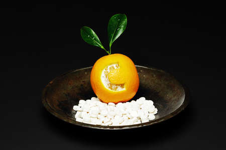 Orange with the letter c engraved, in a bowl with vitamin tablets, Letter c representing vitamin C