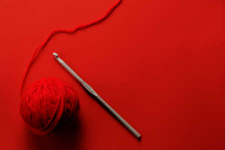 Red wool with crochet needle on red paper background