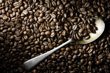Roasted coffee beans flat lay with a steel spoon in dramatic side light. Top view with copy space. Stock Zdjęcie Seryjne