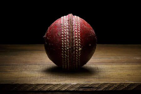 Leather Cricket ball close-up on a wooden surface fine art with copy space Zdjęcie Seryjne