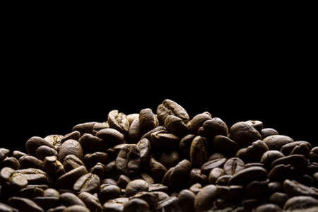 Coffee beans freshly roasted close-up with black background for text space. Stock