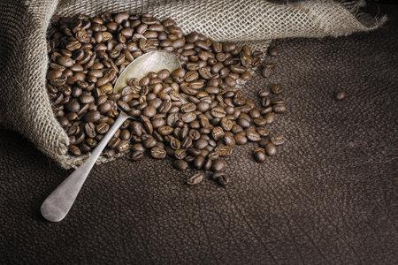 Roasted coffee beans chocolaty toned still life with a hessian bag and a metal vintage spoon on buffalo leather. Zdjęcie Seryjne