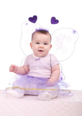 Baby girl in a purple dress sitting in studio
