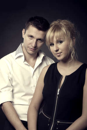 close up portrait of a young couple together on black background