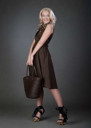 a beautiful blonde woman with handbag in brown dress