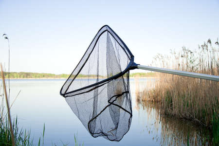 Landing net on the lake with blue sky outside