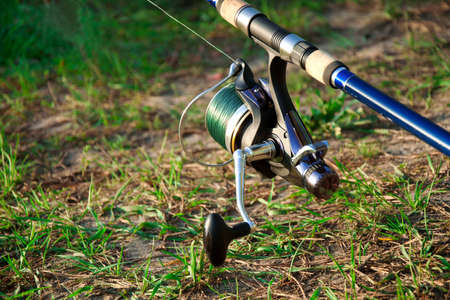 blue fishing reel on the green grass outside Stock Photo - 14538331