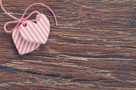 pink hearts on wooden board with pink ribbon Stock Photo - 17355207