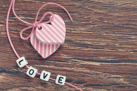 pink hearts on wooden board with pink ribbon and letters Stock Photo